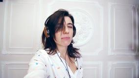 Πορτρέτο της αστείας νέας γυναίκας, κορίτσι, brunette, στο άσπρο πουκάμισο, στα ακουστικά, που ακούει τη μουσική, πυροβολεί το βί φιλμ μικρού μήκους