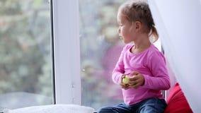 Πορτρέτο της αστείας χαριτωμένης συνεδρίασης μικρών κοριτσιών στη στρωματοειδή φλέβα παραθύρων και της κατανάλωσης του μήλου φιλμ μικρού μήκους