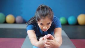 Πορτρέτο της βέβαιας ασιατικής νέας γυναίκας που κάνει την τεντώνοντας προσιτότητα άσκησης έξω στο γυμνό πόδι με το χέρι απόθεμα βίντεο