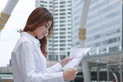 Πορτρέτο της βέβαιας νέας ασιατικής επιχειρησιακής γυναίκας που αναλύει τα διαγράμματα ή τη γραφική εργασία στο εξωτερικό γραφείο Στοκ Εικόνες