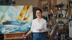 Πορτρέτο της βέβαιων παλέτας και του πινέλου εκμετάλλευσης ζωγράφων κοριτσιών που στέκονται κοντά seascape που εξετάζει τη κάμερα απόθεμα βίντεο