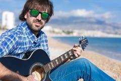 Πορτρέτο της γενειοφόρου κιθάρας παιχνιδιού ατόμων και εξέταση τη κάμερα Στοκ φωτογραφία με δικαίωμα ελεύθερης χρήσης