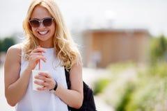 Πορτρέτο της γελώντας ξανθής γυναίκας με να αναζωογονήσει το ποτό υπαίθρια στοκ εικόνα με δικαίωμα ελεύθερης χρήσης
