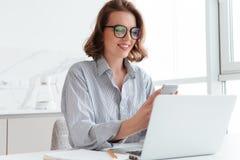 Πορτρέτο της γοητείας της γυναίκας στα γυαλιά και το ριγωτό πουκάμισο που χρησιμοποιούν το MO Στοκ Φωτογραφίες