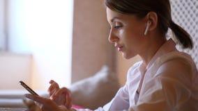 Πορτρέτο της γυναίκας με τα earpods που χρησιμοποιούν το smartphone απόθεμα βίντεο