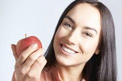 Πορτρέτο της γυναίκας με την όμορφη εκμετάλλευση Apple χαμόγελου Στοκ Φωτογραφίες
