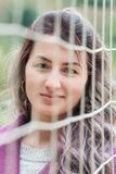 Πορτρέτο της γυναίκας πίσω από ένα πλέγμα Στοκ Εικόνες