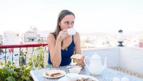 Πορτρέτο της γυναίκας που έχει ένα πρόγευμα στον καφέ στο πεζούλι στοκ εικόνα