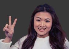 Πορτρέτο της γυναίκας που κάνει το σημάδι ειρήνης με το γκρίζο υπόβαθρο Στοκ φωτογραφίες με δικαίωμα ελεύθερης χρήσης