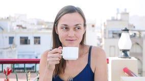 Πορτρέτο της γυναίκας που πίνει το καυτό ποτό ενώ έχοντας ένα πρόγευμα στο πεζούλι στοκ φωτογραφία με δικαίωμα ελεύθερης χρήσης