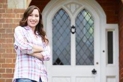 Πορτρέτο της γυναίκας που στέκεται έξω από τη μπροστινή πόρτα του σπιτιού στοκ φωτογραφία με δικαίωμα ελεύθερης χρήσης