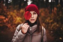 Πορτρέτο της γυναίκας που στέκεται στο δάσος φθινοπώρου και το μισό καλύψεων από το πρόσωπό της με το φύλλο φθινοπώρου Στοκ Φωτογραφίες