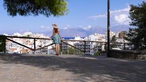 Πορτρέτο της γυναίκας στο θερινό καπέλο που κοιτάζει στο πανόραμα πόλεων, Κρήτη απόθεμα βίντεο