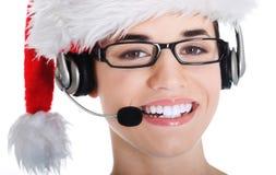 Πορτρέτο της γυναίκας στο καπέλο santa με το μικρόφωνο και το ακουστικό. Στοκ φωτογραφία με δικαίωμα ελεύθερης χρήσης