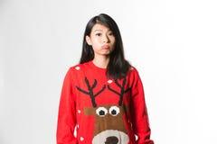 Πορτρέτο της γυναίκας στο πουλόβερ Χριστουγέννων που στέκεται κάνοντας το αστείο πρόσωπο πέρα από το γκρίζο υπόβαθρο Στοκ Φωτογραφία