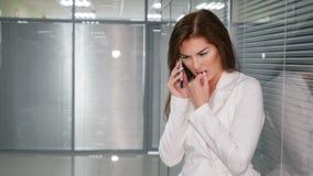 Πορτρέτο της δυστυχισμένης νέας επιχειρηματία που μιλά στο τηλέφωνο στην αρχή στοκ εικόνες με δικαίωμα ελεύθερης χρήσης