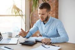 Πορτρέτο της δυστυχισμένης ώριμης γενειοφόρου εργασίας λογιστών στο γραφείο επιχείρησης, που είναι ματαιωμένα κέρδη ένα υπολογισμ Στοκ φωτογραφία με δικαίωμα ελεύθερης χρήσης