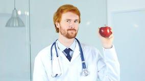 Πορτρέτο της εκμετάλλευσης η κόκκινη Apple και εξέταση γιατρών τη κάμερα Στοκ εικόνα με δικαίωμα ελεύθερης χρήσης