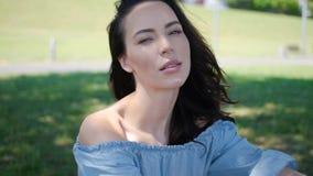 Πορτρέτο της ελκυστικής γυναίκας brunette στην μπλε συνεδρίαση φορεμάτων σε ένα πάρκο απόθεμα βίντεο
