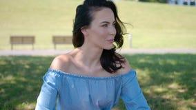 Πορτρέτο της ελκυστικής γυναίκας brunette στην μπλε συνεδρίαση φορεμάτων σε ένα πάρκο φιλμ μικρού μήκους