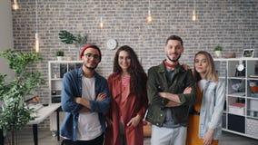 Πορτρέτο της ελκυστικής επιχειρησιακής ομάδας νέων που στέκεται στο χαμόγελο γραφείων φιλμ μικρού μήκους