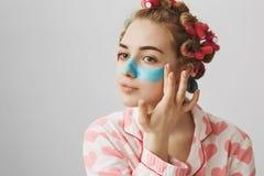 Πορτρέτο της ελκυστικής θηλυκής γυναίκας στα τρίχα-ρόλερ που εφαρμόζει την μπλε μάσκα προσώπου στα μάγουλα και τη μύτη, που κοιτά στοκ φωτογραφία με δικαίωμα ελεύθερης χρήσης
