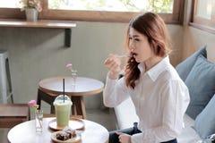 Πορτρέτο της ελκυστικής νέας ασιατικής γυναίκας με το δίκρανο που τρώει brownie το κέικ στον καφέ στοκ φωτογραφίες