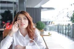 Πορτρέτο της ελκυστικής νέας ασιατικής ομιλίας επιχειρησιακών γυναικών στο τηλέφωνο στην αρχή στοκ εικόνες