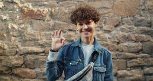 Πορτρέτο της ελκυστικής νέας κυρίας hipster που παρουσιάζει ΕΝΤΑΞΕΙ χειρονομία που στέκεται έξω απόθεμα βίντεο