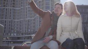 Πορτρέτο της ελκυστικής συνεδρίασης cuople στην οδό πόλεων που μιλά και που χαμογελά Το ζεύγος που κουβεντιάζει συζητώντας την απ απόθεμα βίντεο