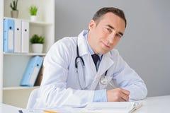 Πορτρέτο της ενήλικης συνεδρίασης γιατρών στο γραφείο του στοκ φωτογραφίες