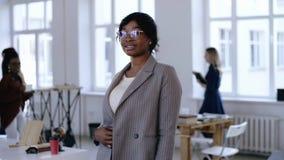 Πορτρέτο της επαγγελματικής νέας αφρικανικής επιχειρησιακής γυναίκας επιχειρηματιών eyeglasses που θέτουν στο σύγχρονο ελαφρύ γρα απόθεμα βίντεο