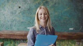 Πορτρέτο της επιτυχούς όμορφης ξανθής επιχειρηματία στο coworking διάστημα σοφιτών Το θηλυκό κρατά το έγγραφο, χαμόγελο φιλμ μικρού μήκους