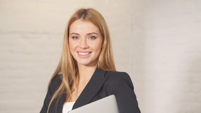 Πορτρέτο της επιχειρηματία με το lap-top, που εξετάζει τη κάμερα σε ένα σύγχρονο γραφείο απόθεμα βίντεο