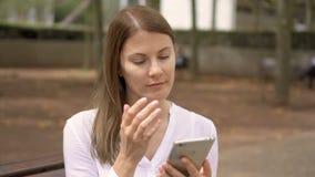 Πορτρέτο της επιχειρηματία στην άσπρη συνεδρίαση πουκάμισων στο πάρκο Επαγγελματικό θηλυκό που χρησιμοποιεί το κινητό τηλέφωνο απόθεμα βίντεο