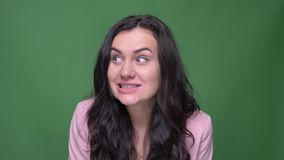 Πορτρέτο της επιχειρηματία brunette στο ρόδινο σακάκι που κάνει τα αστεία πρόσωπα στη κάμερα στο πράσινο υπόβαθρο απόθεμα βίντεο