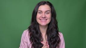 Πορτρέτο της επιχειρηματία brunette στο ρόδινο σακάκι που παρουσιάζει χέρια κυμάτων ικανοποίησής της σε κάποιο στο πράσινο υπόβαθ απόθεμα βίντεο