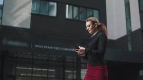 Πορτρέτο της επιχειρησιακής γυναίκας με τα κινητά τηλεφωνικά χέρια το κορίτσι στα επιχειρησιακά ενδύματα περπατά κατά μήκος της ο απόθεμα βίντεο