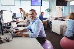 Πορτρέτο της εργασίας επιχειρηματιών χαμόγελου στο γραφείο καθμένος στη σφαίρα άσκησης Στοκ φωτογραφίες με δικαίωμα ελεύθερης χρήσης