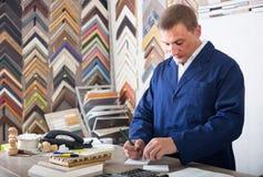 Πορτρέτο της εργασίας πωλητών ατόμων με τα πλαίσια εικόνων στο ατελιέ στοκ εικόνες