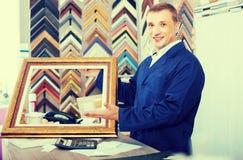 Πορτρέτο της εργασίας πωλητών ατόμων με τα πλαίσια εικόνων στο ατελιέ στοκ φωτογραφίες με δικαίωμα ελεύθερης χρήσης