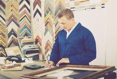 Πορτρέτο της εργασίας πωλητών ατόμων με τα πλαίσια εικόνων στο ατελιέ στοκ εικόνες με δικαίωμα ελεύθερης χρήσης