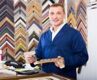 Πορτρέτο της εργασίας πωλητών ατόμων με τα πλαίσια εικόνων στο ατελιέ στοκ εικόνα