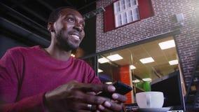 Πορτρέτο της ευτυχούς αφρικανικής συνεδρίασης επιχειρηματιών σε έναν καφέ και της εργασίας στο lap-top φιλμ μικρού μήκους