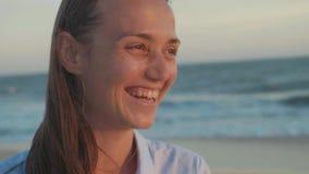 Πορτρέτο της ευτυχούς γυναίκας που εξετάζει τη κάμερα και που γελά στην παραλία σε σε αργή κίνηση απόθεμα βίντεο