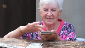 Πορτρέτο της ευτυχούς δέσμης εκμετάλλευσης γιαγιάδων των χρημάτων στα χέρια και του διασκορπίζοντας ξένου νομίσματος στο γραφείο  απόθεμα βίντεο