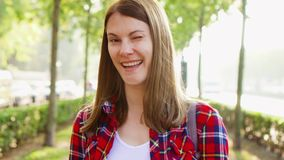 Πορτρέτο της ευτυχούς εύθυμης νέας γυναίκας που απολαμβάνει τη φύση Περπάτημα στο πράσινο πάρκο που χαμογελά στη κάμερα απόθεμα βίντεο