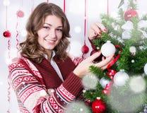 Πορτρέτο της ευτυχούς νέας γυναίκας που διακοσμεί το χριστουγεννιάτικο δέντρο Στοκ Εικόνες