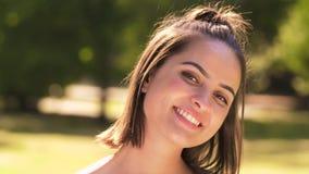 Πορτρέτο της ευτυχούς νέας γυναίκας στο θερινό πάρκο απόθεμα βίντεο