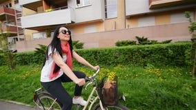 Πορτρέτο της ευτυχούς νέας γυναίκας στο ποδήλατο Έχει πολλή διασκέδαση φιλμ μικρού μήκους